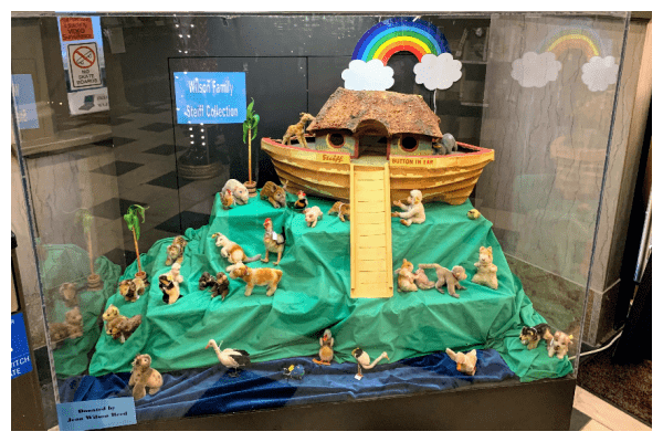Photograph of a large display case with a Steiff ark and approximately twenty small Steiff toys around it. The ark is sitting on green fabric. A rainbow is hanging above the ark.